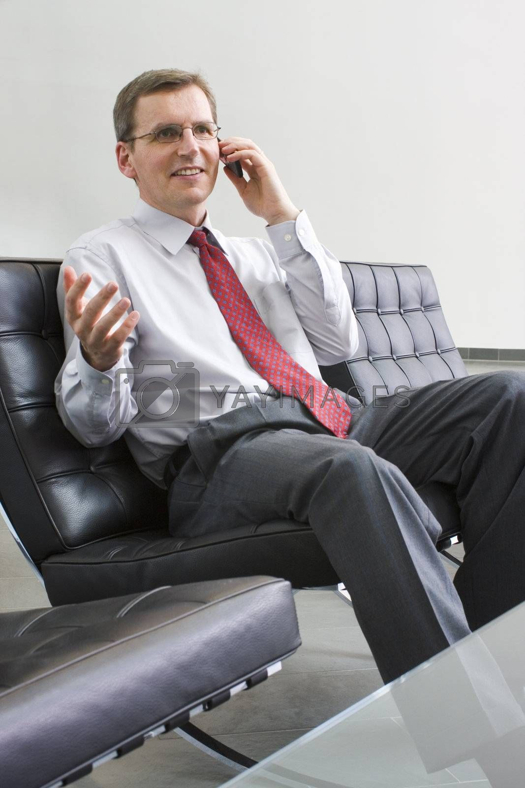 Businessman or politician talking on cell phone while sitting in a chair of leather
