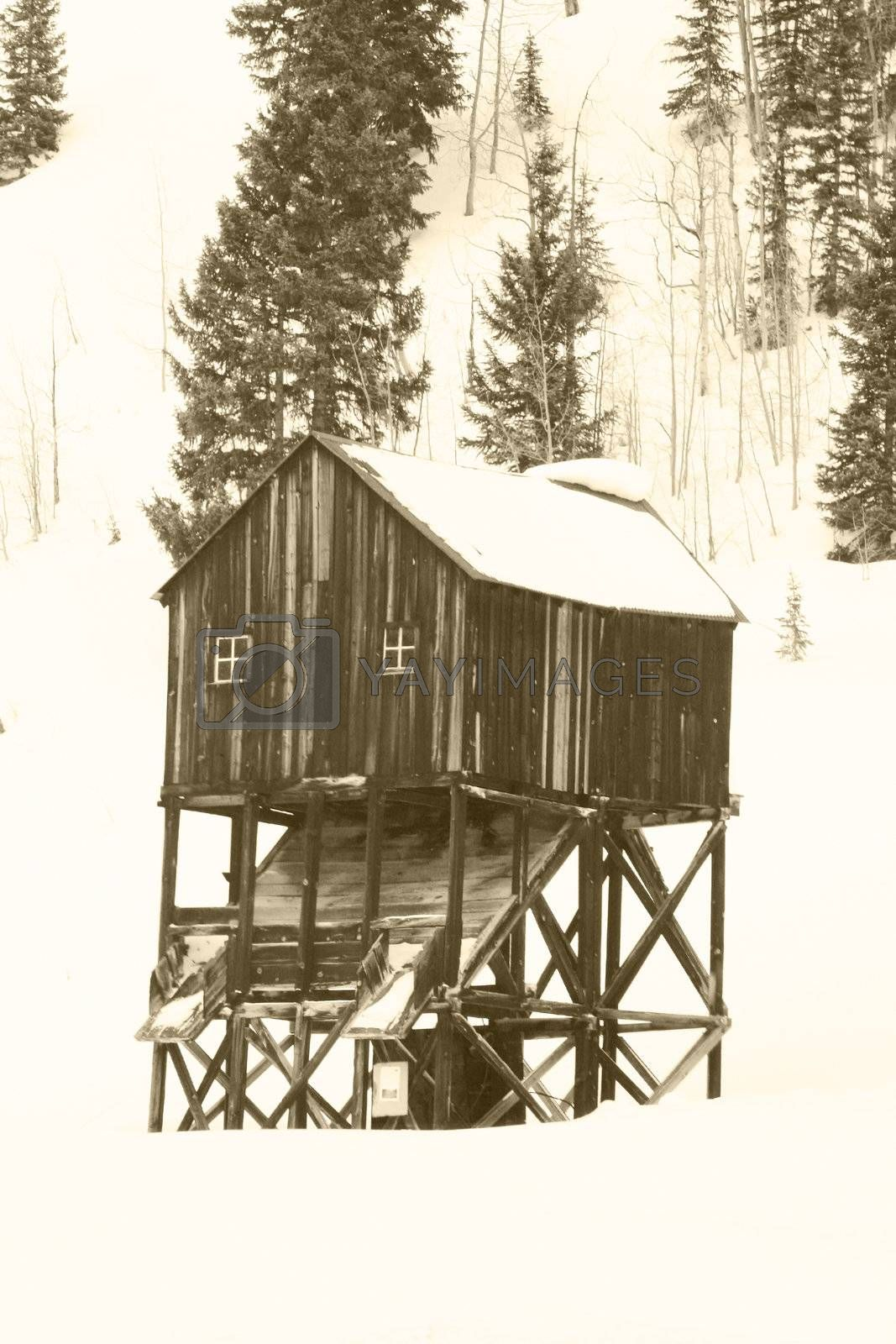 Old mining hut in mountains with snow