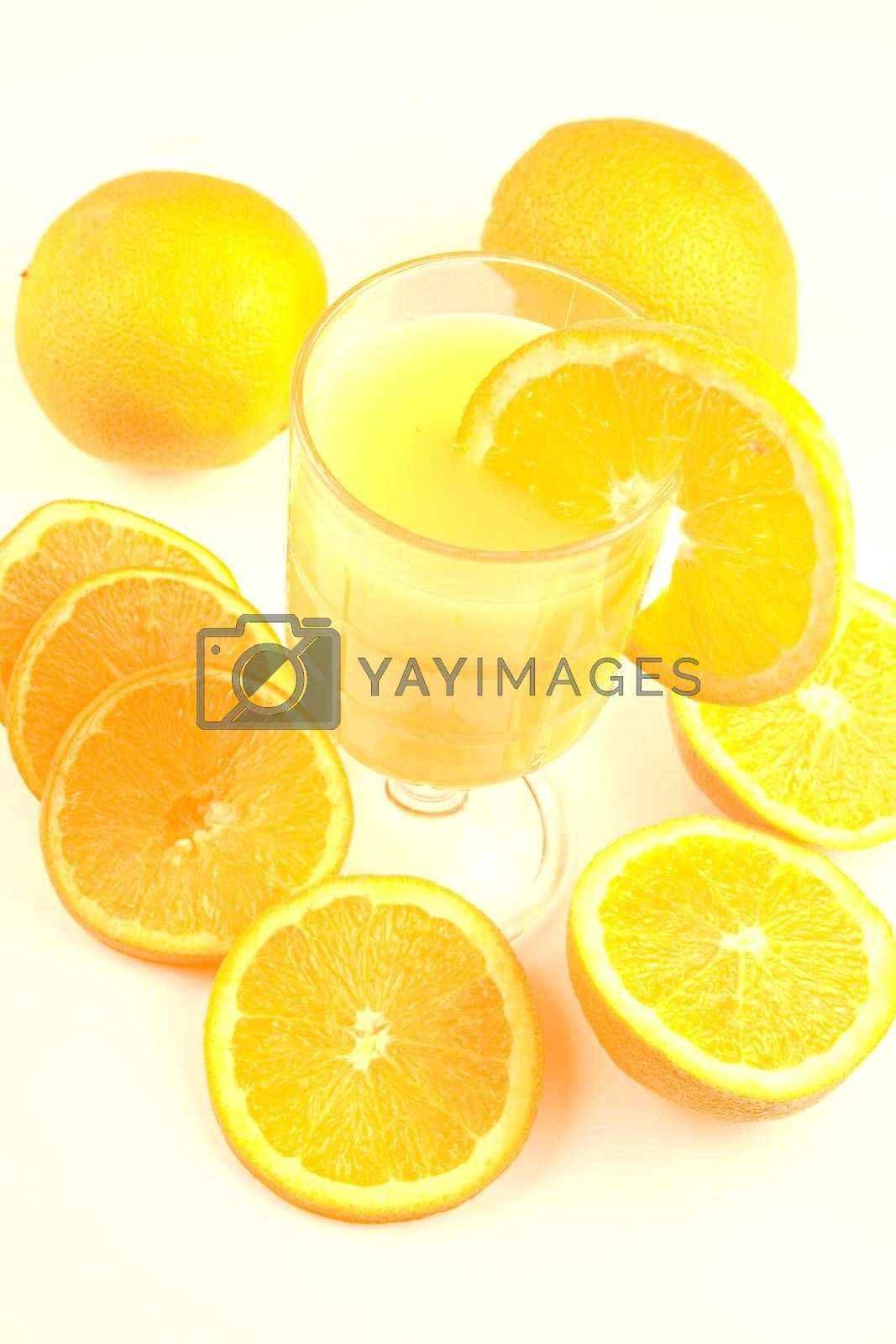 Glass of orange juice surounded by oranges