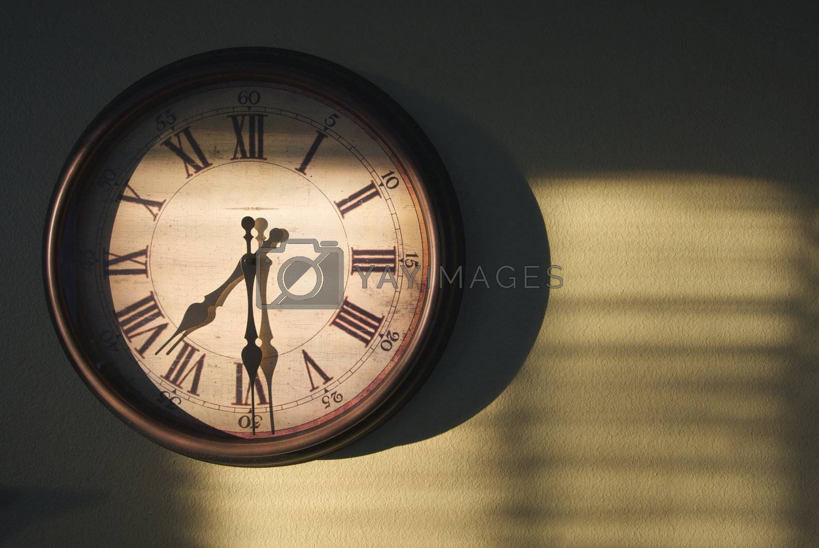 Antique Clock on an olive green wall with dramatic evening light and shadows.