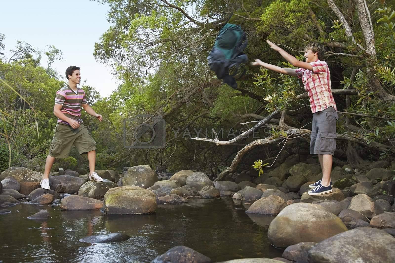 Young Man Throwing Backpack Across Creek