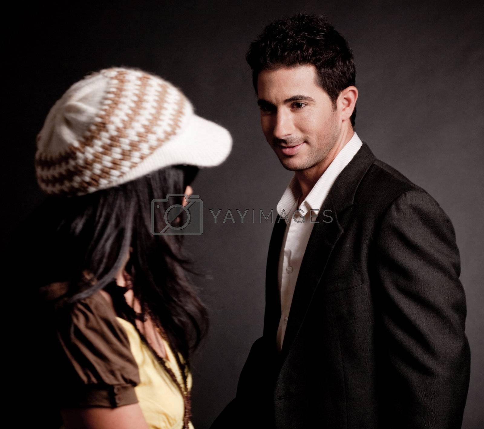 Attractive young man looking at woman on isolated black background