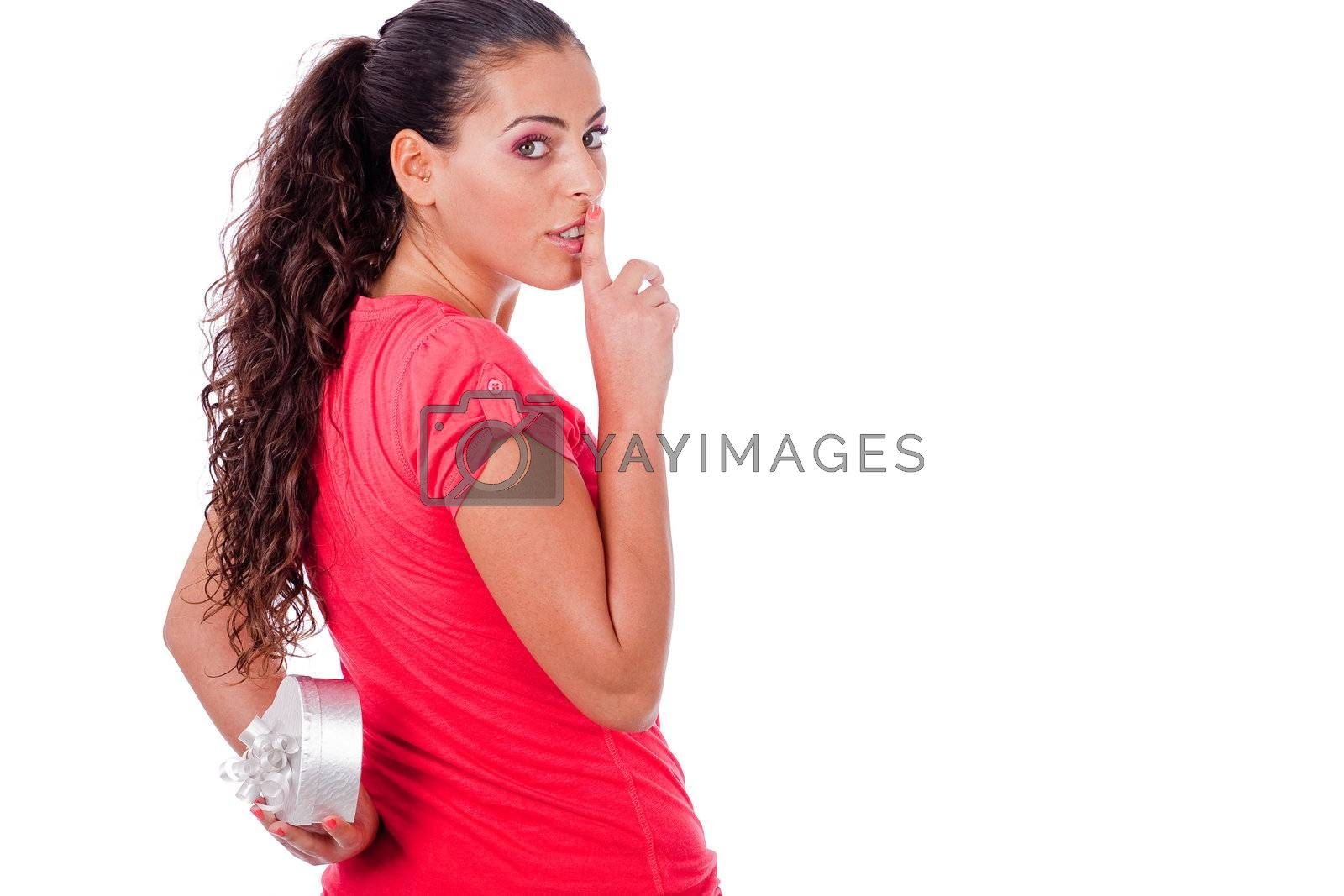 Cute girl hides a heart symbol on her back on isolated white background