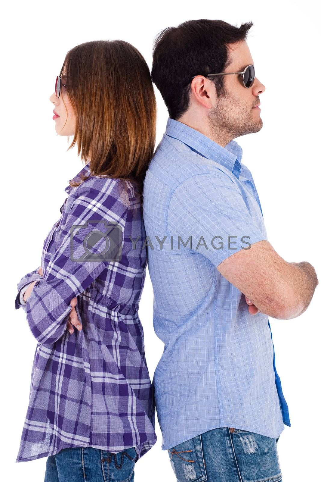Young couple standing back to back wearing sunglasses on a white background