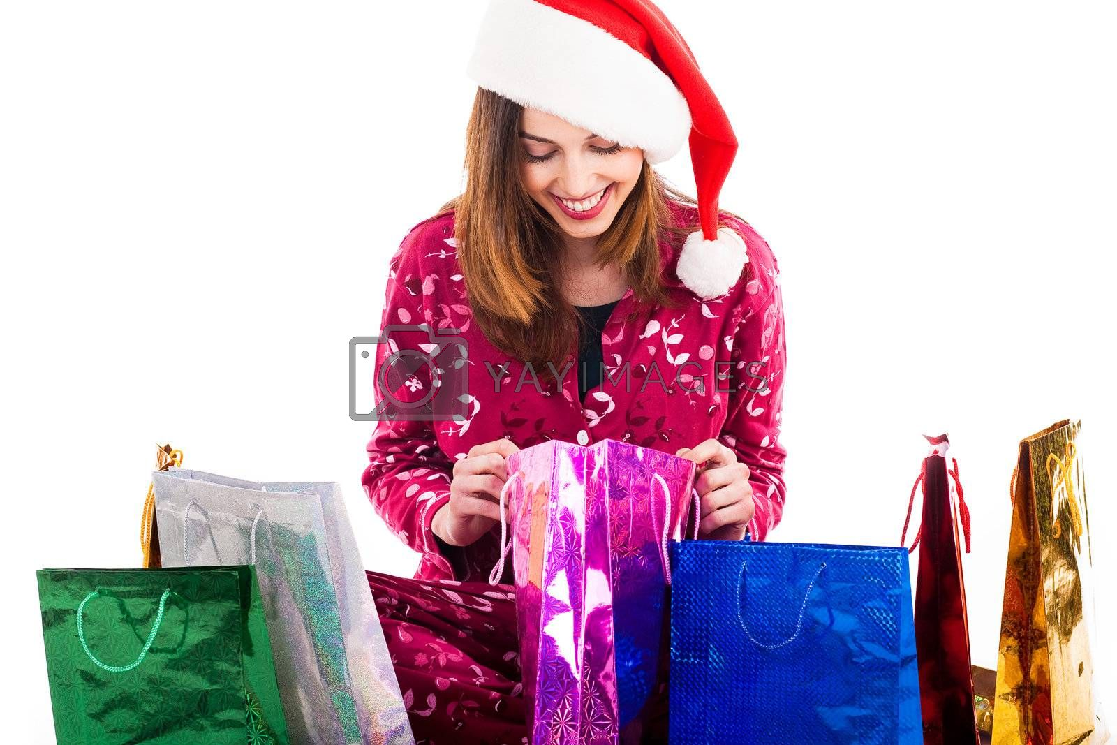 Young girl with santa cap checking into her shopping bags on a isolated white background