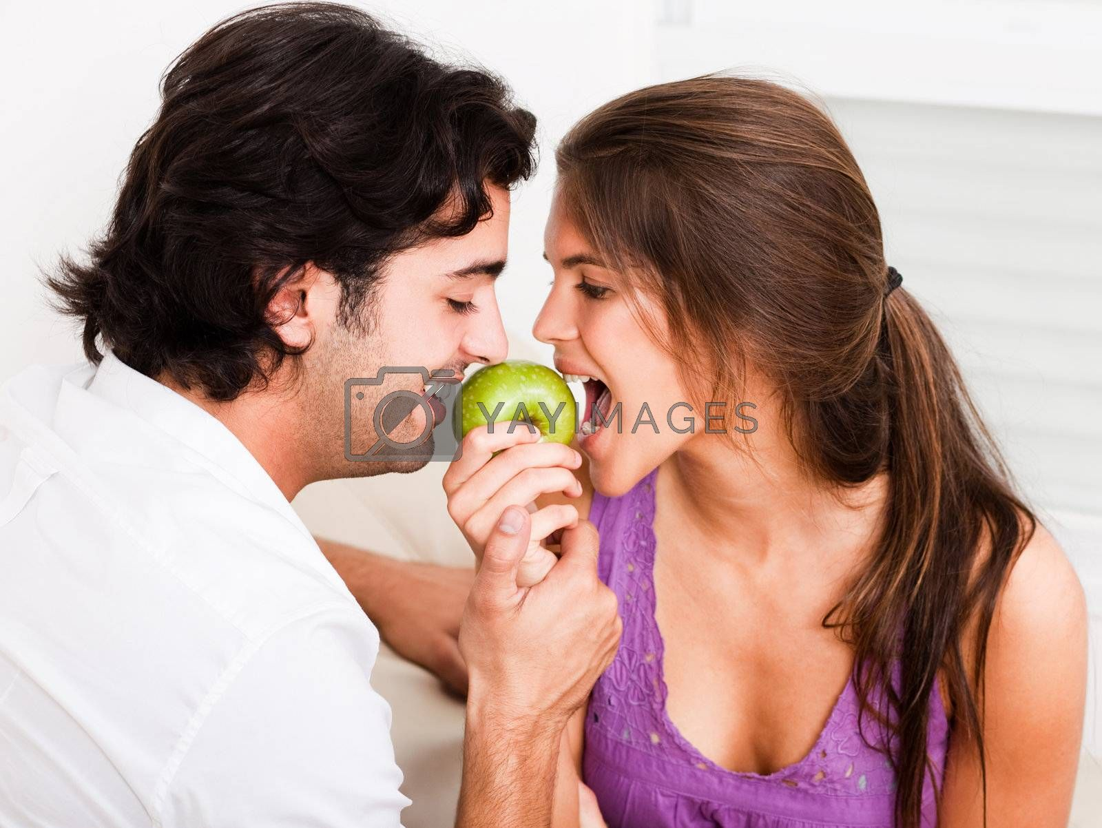 closeup of young couple playfully biting green apple at a time