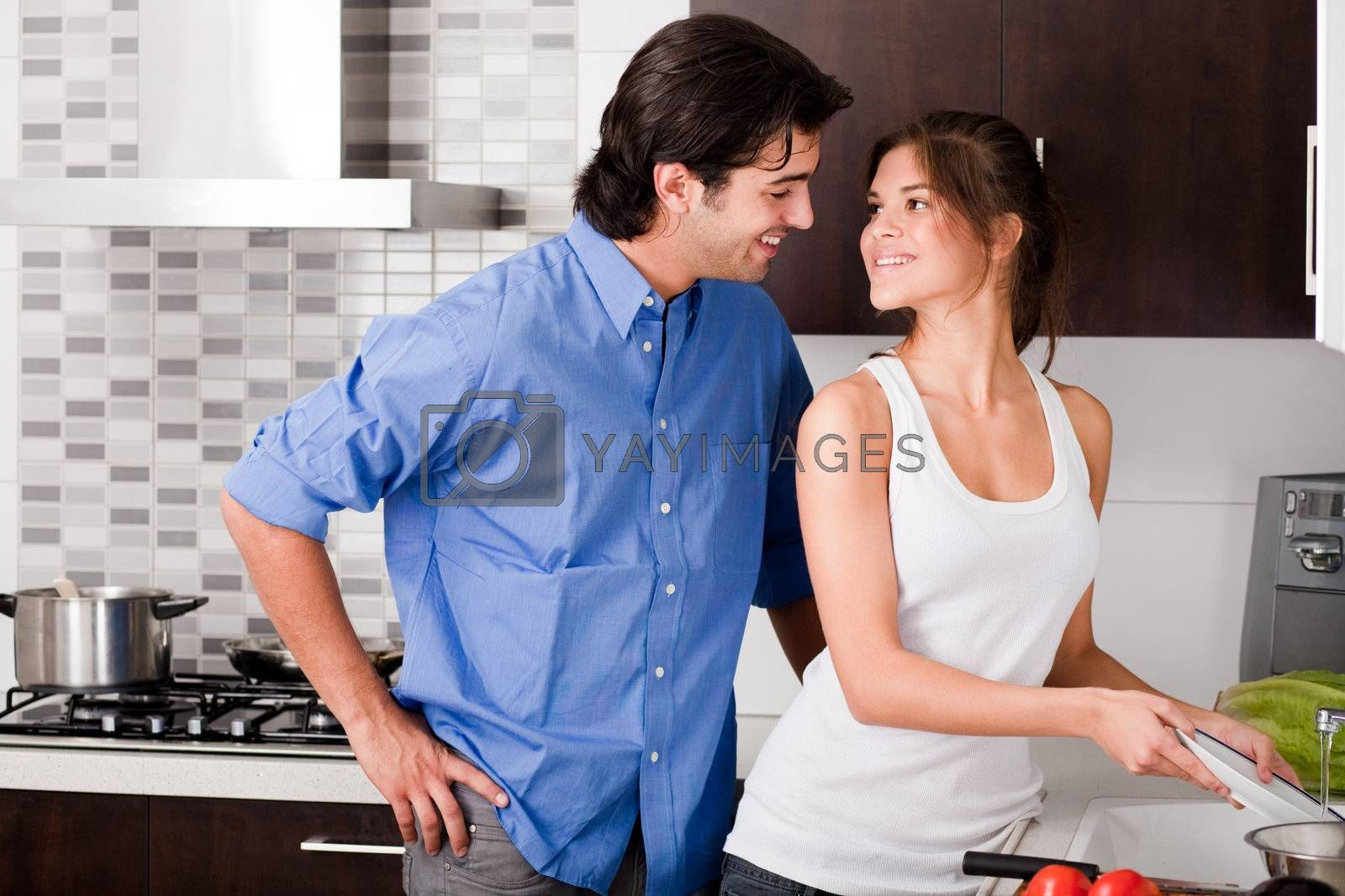 smiling young couple enjoying their love in kitchen