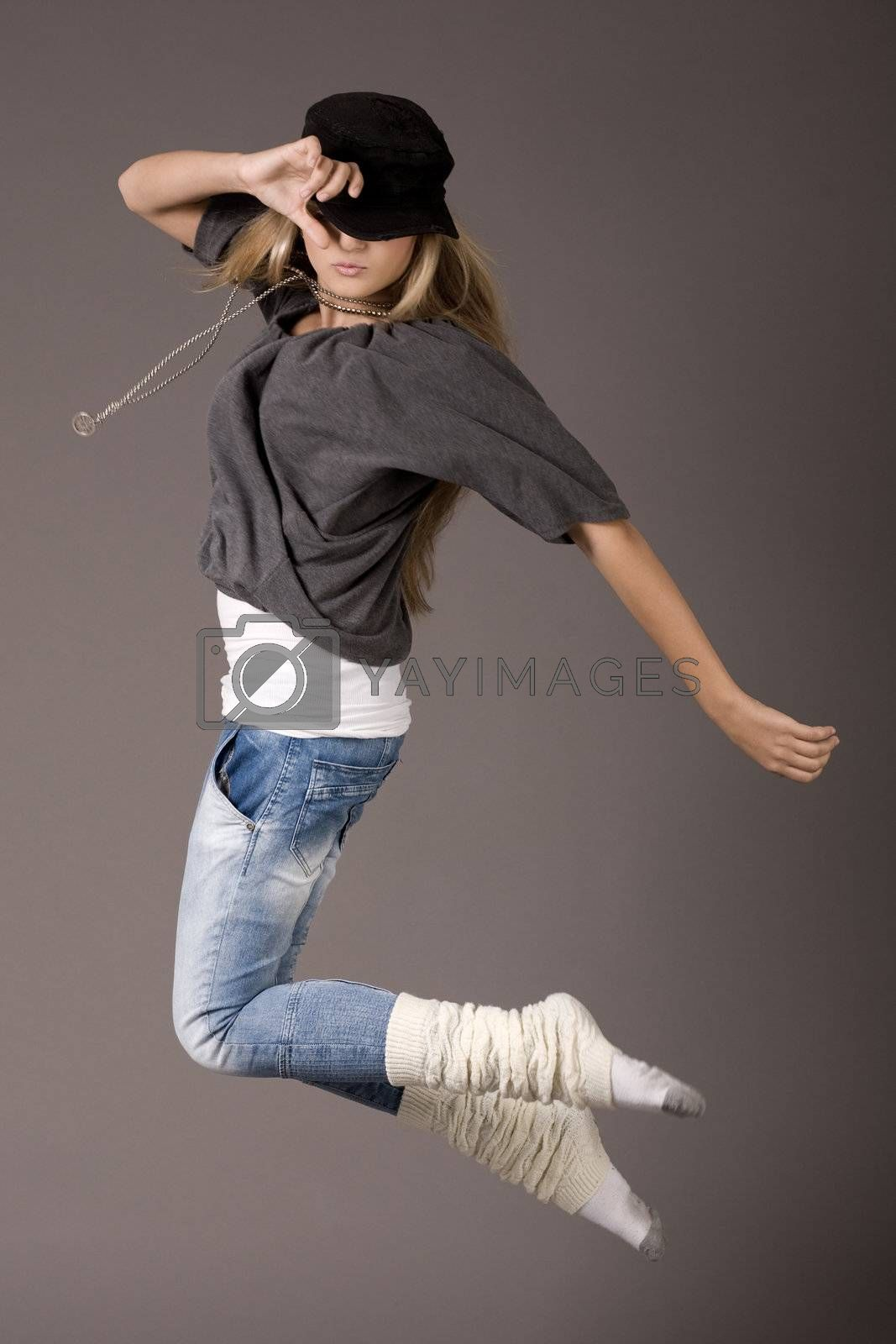 Young women jumping during her dance on grey background