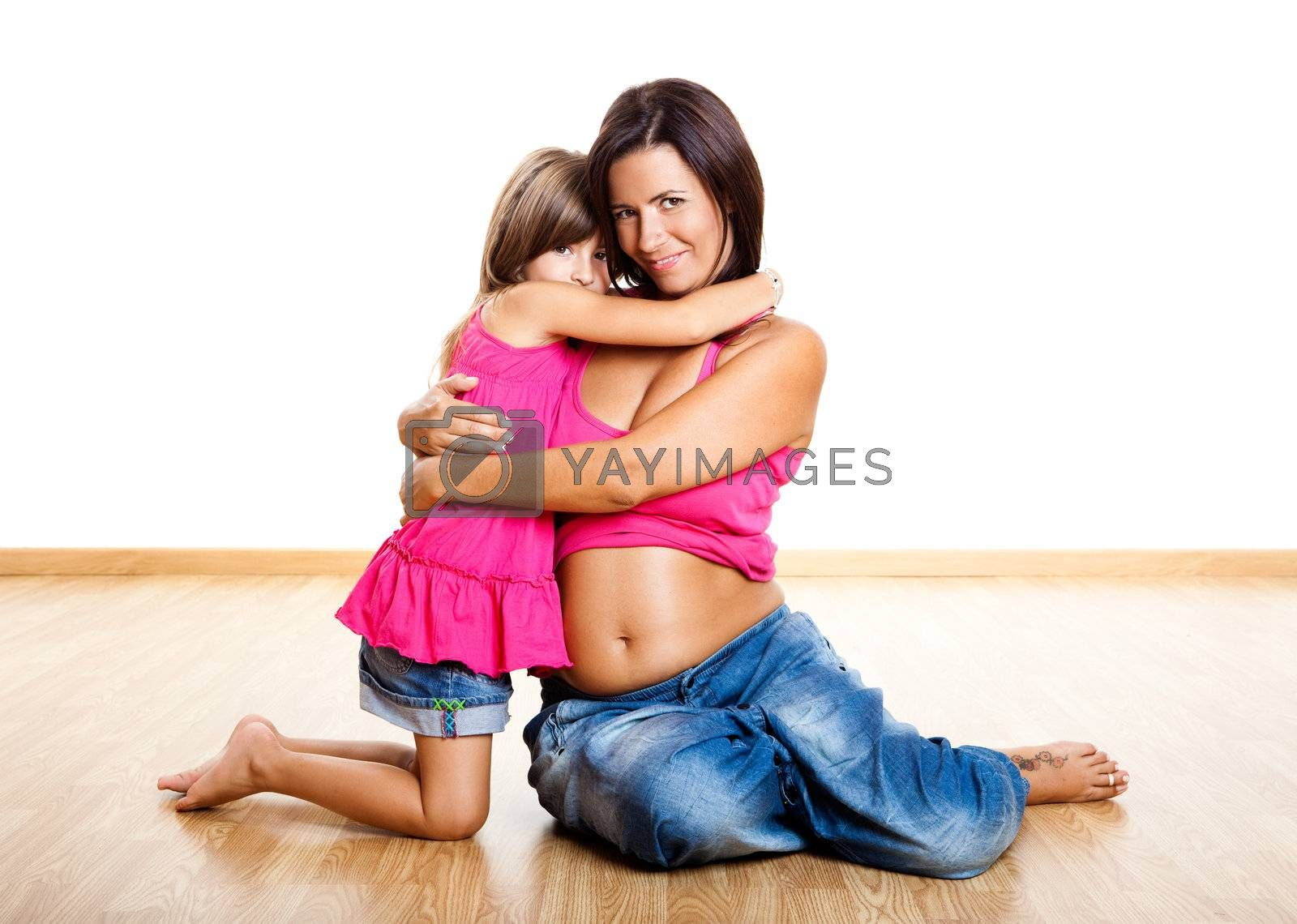 Beautiful pregnant mother with her daughter isolated on white
