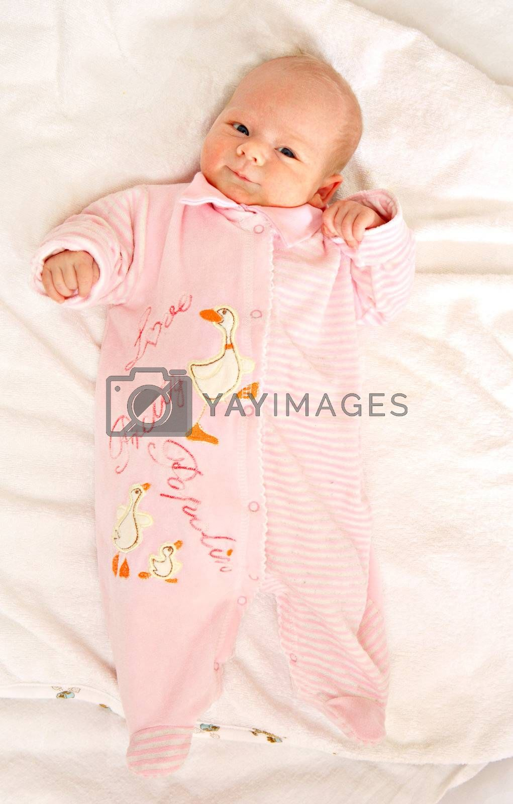The newborn girl in pink clothes on a white background