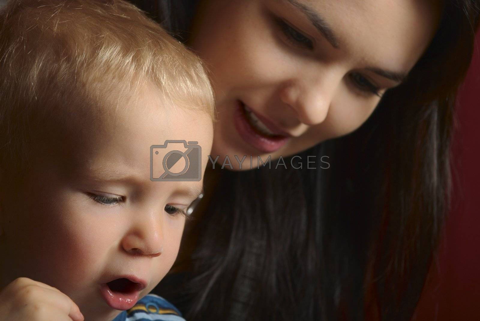 Mother and child reading together a book.