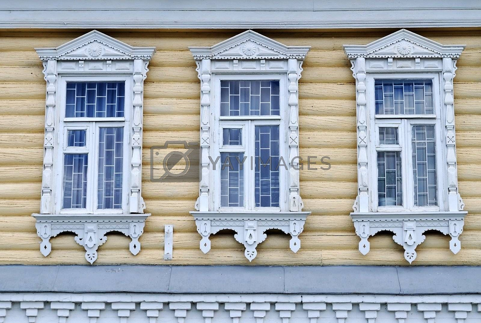 Windows of wooden building with traditional for Russian village trimming