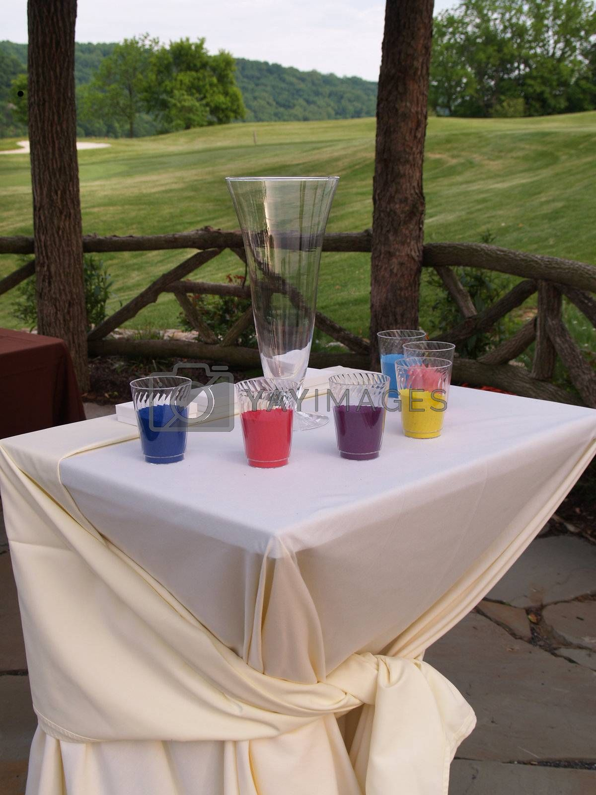 glasses of colored sand sitting on a table covered with a white tablecloth to be used for a wedding ceremony