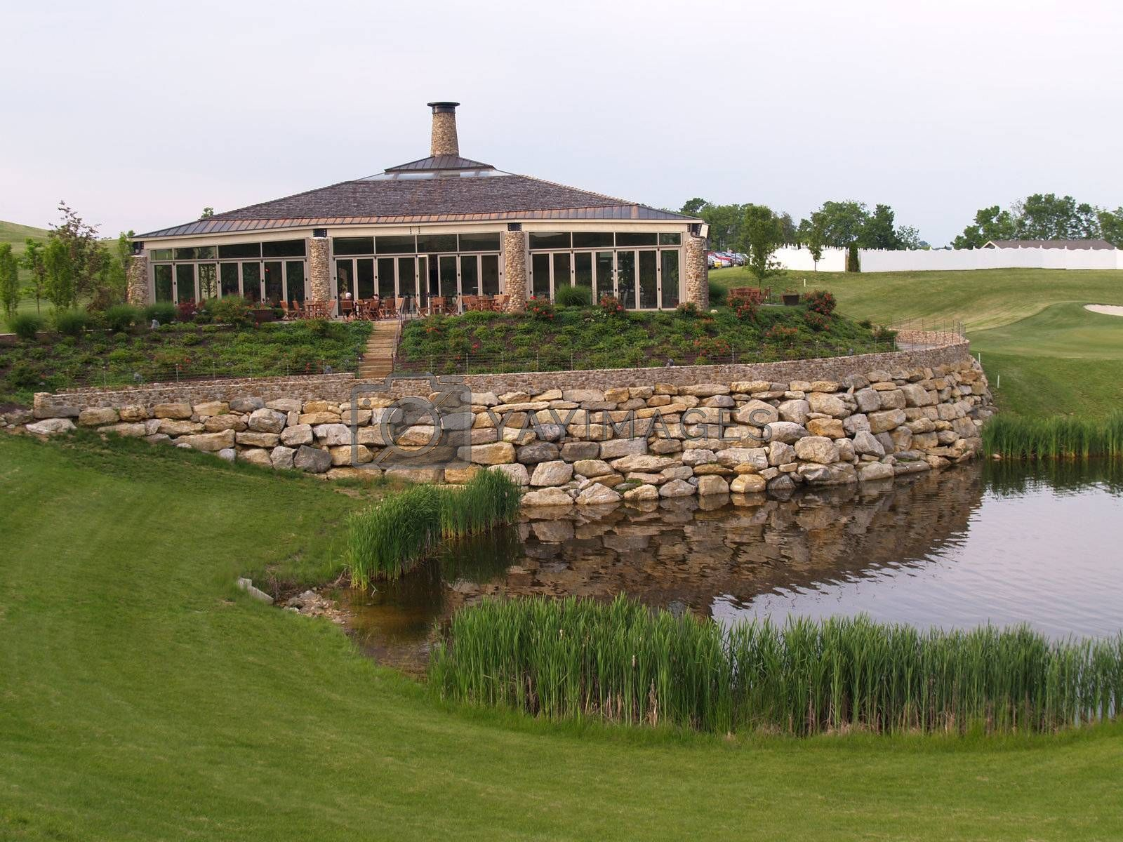 exterior of a modern stone building by a golf course and calm pond