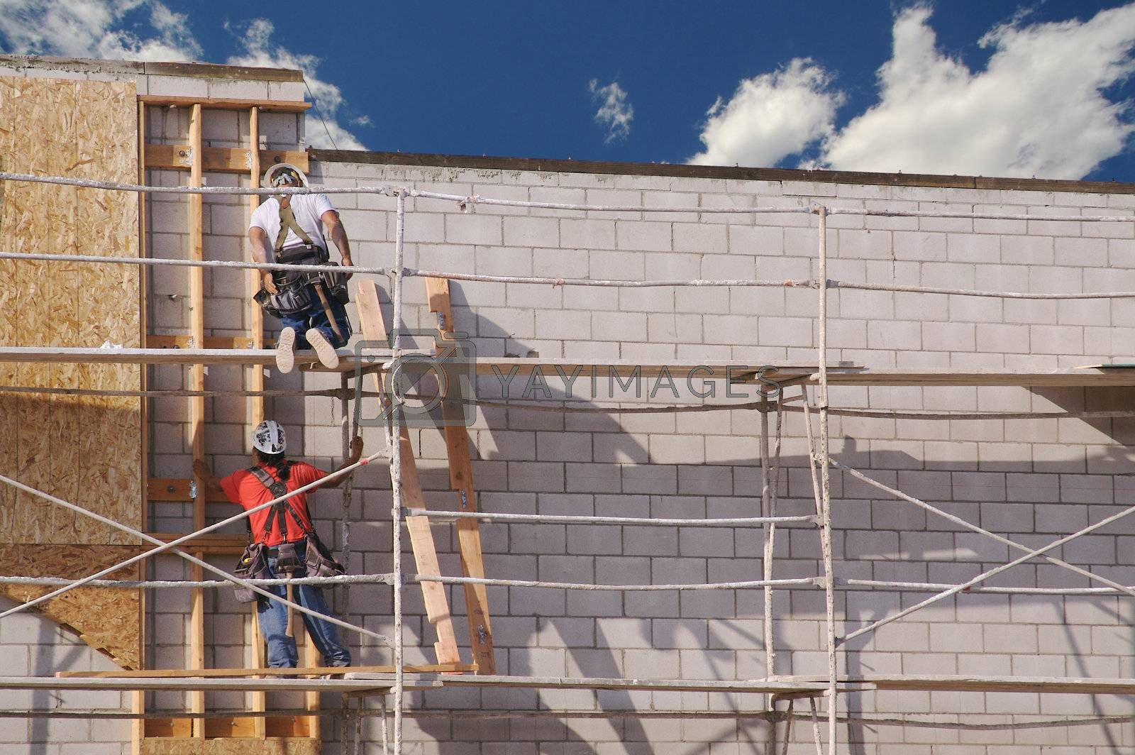 Carpenters working diligently along scaffolding one summer morning.