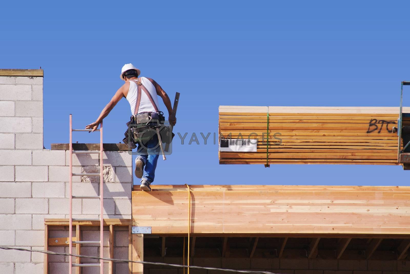 Carpenter climbing up ladder at a construction scene.