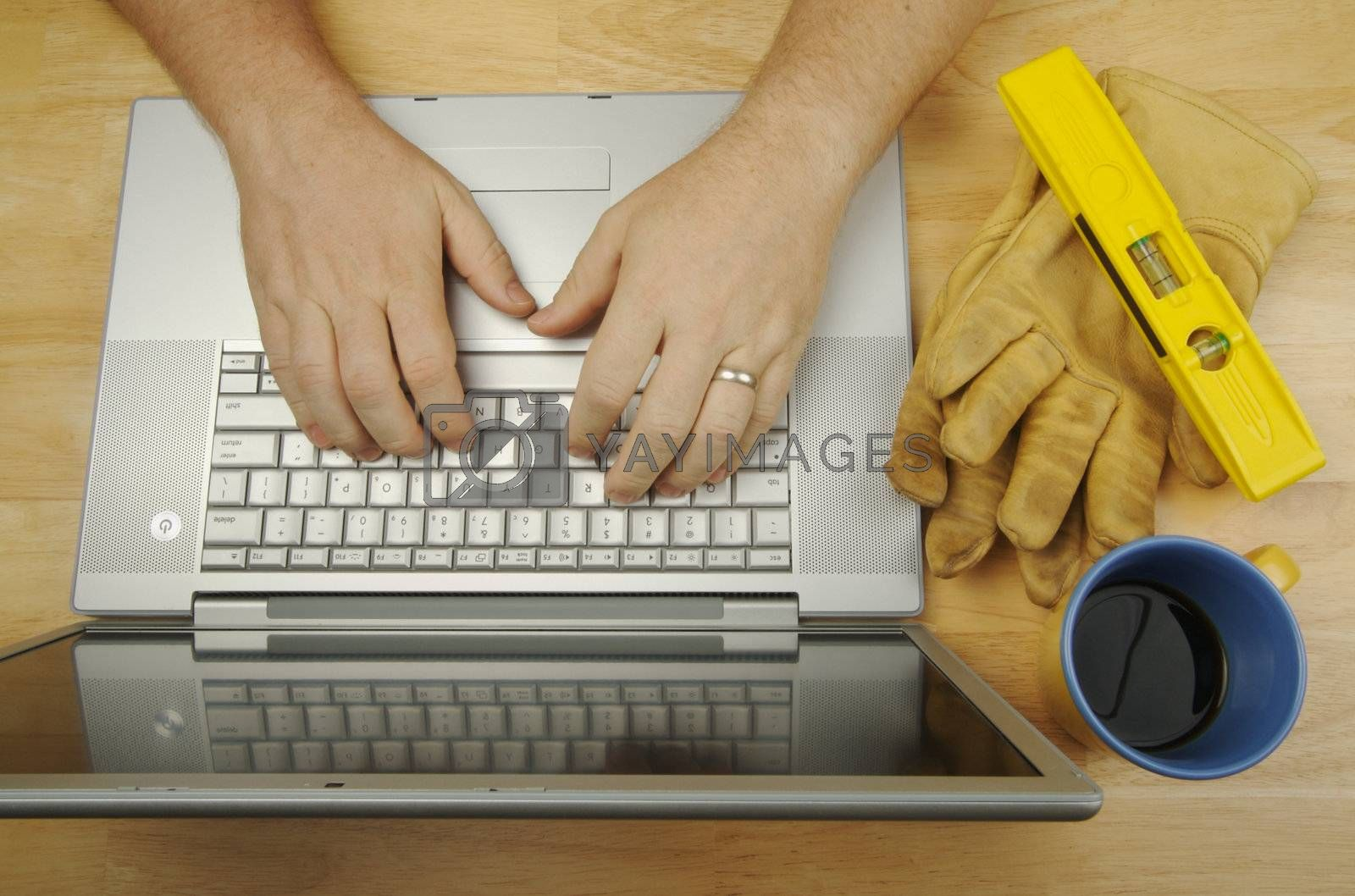 Contractor Reviews Project on Laptop with level, gloves and coffee to his side. Great image for online information regarding home improvement, additions, remodeling or construction.