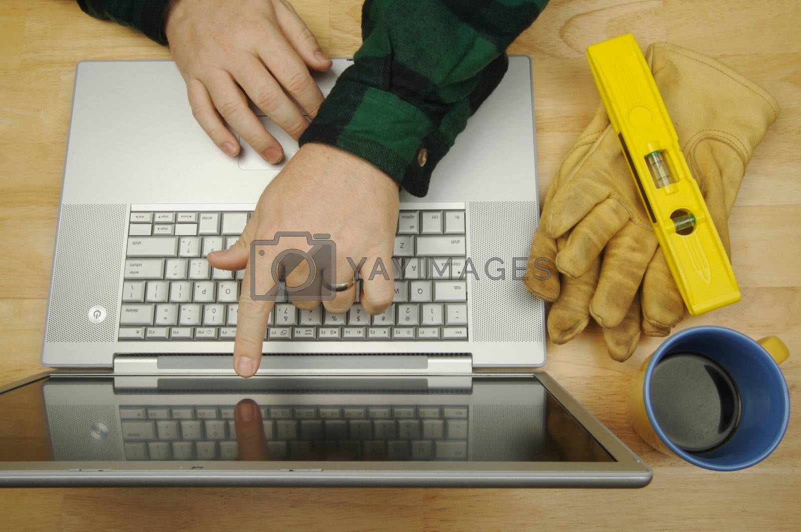 Contractor Points & Reviews Project on Laptop with level, gloves and coffee to his side. Great image for online information regarding home improvement, additions, remodeling or construction.
