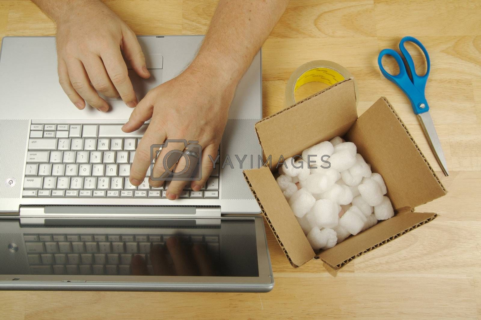 Businessman Works on Laptop with Packaging materials at his side.