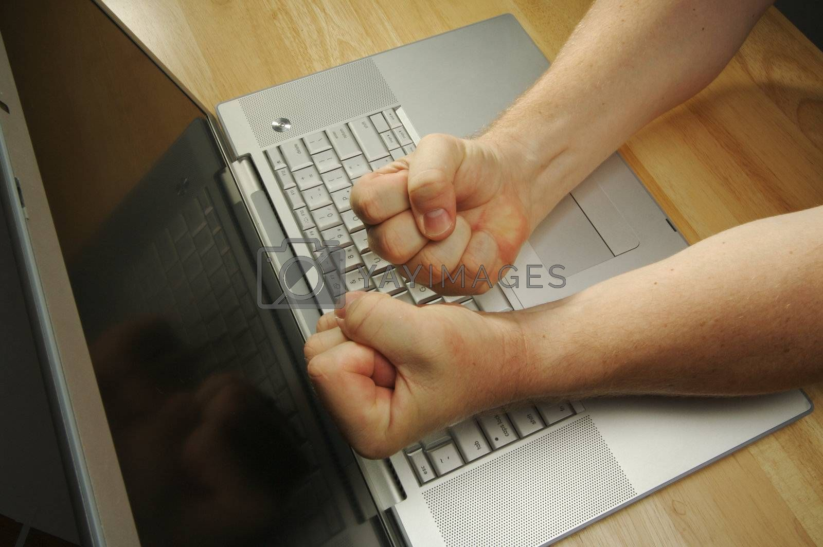 Frustrated businessman shows his frustration while working on his laptop.