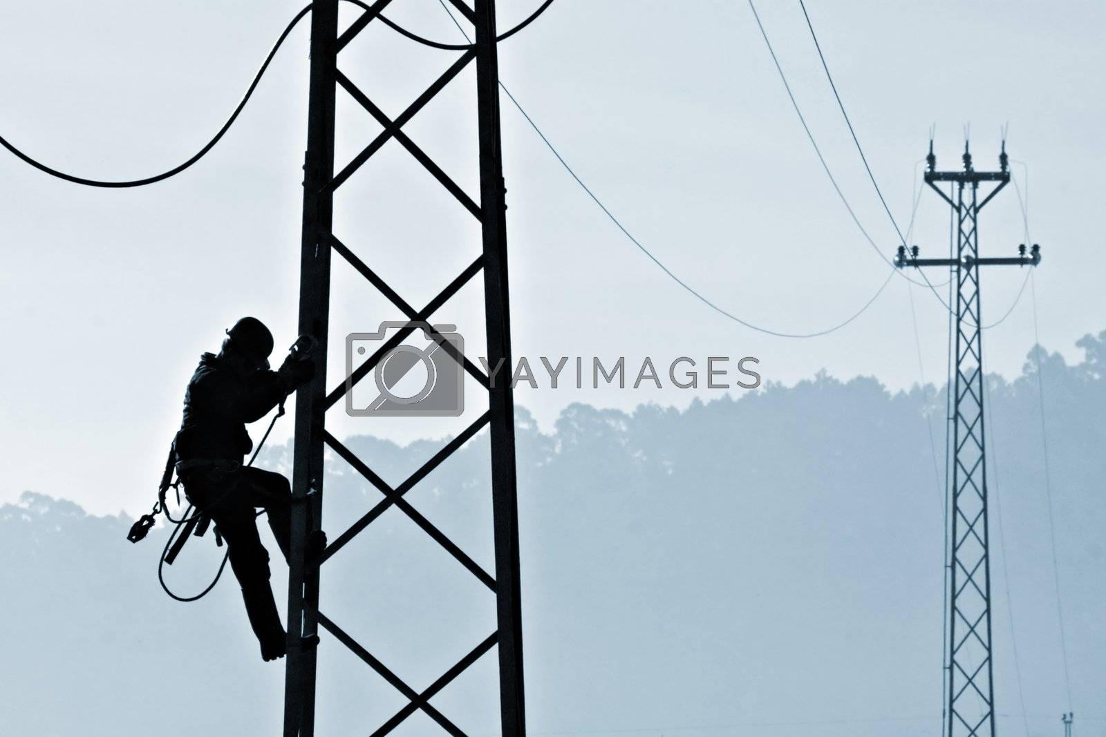 Backlit powerplant worker descending from tower