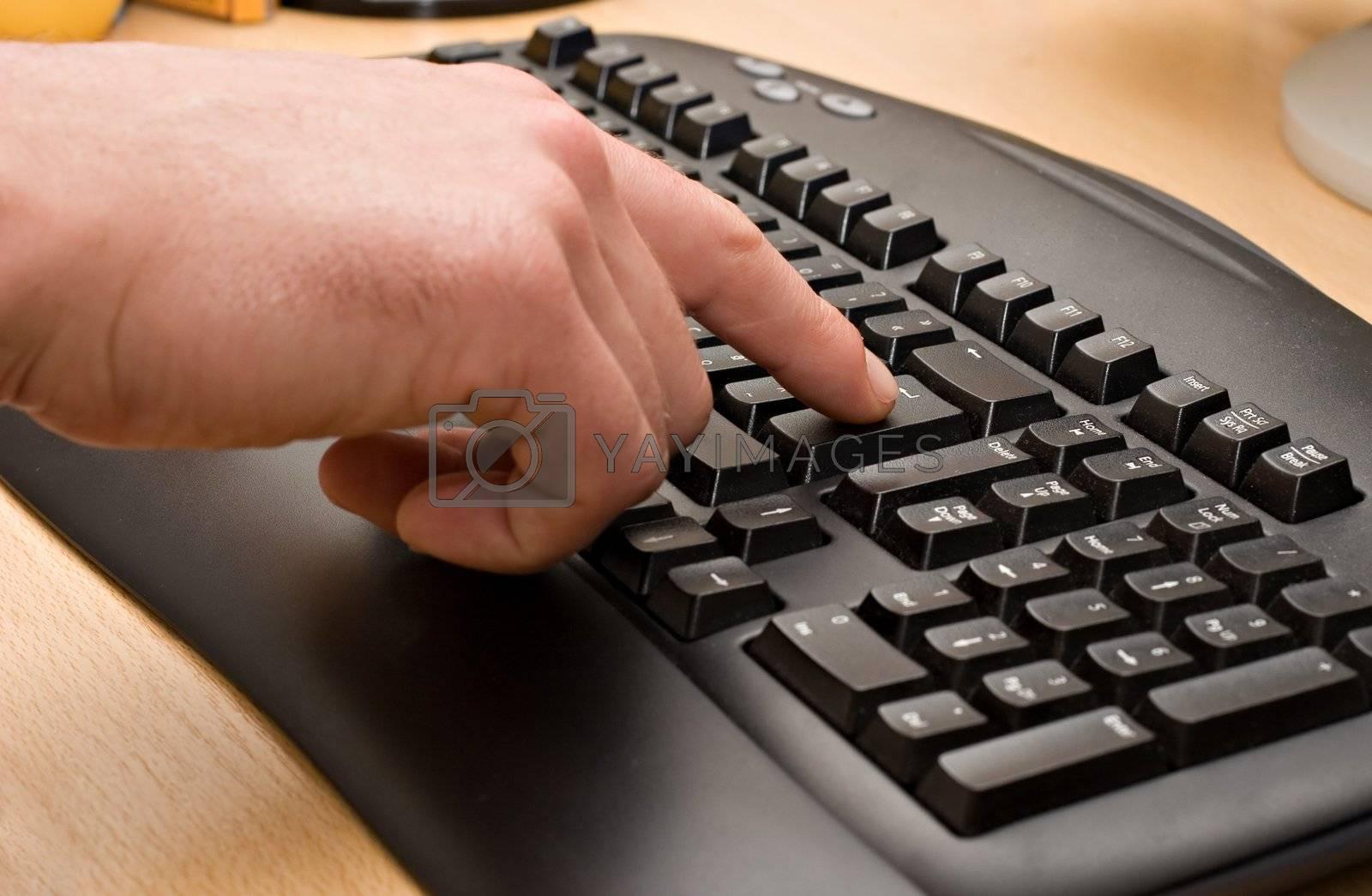 Typing. Pressing Enter Key. Black keyboard on wooden table.