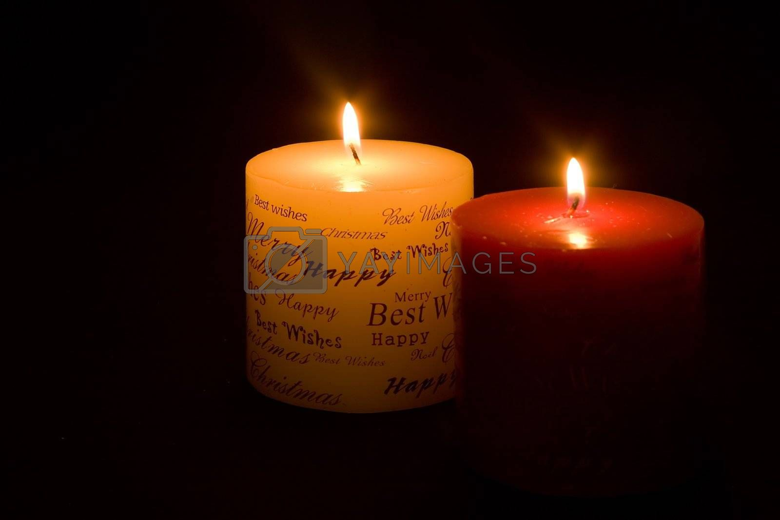 Lit Christmas candles on black background