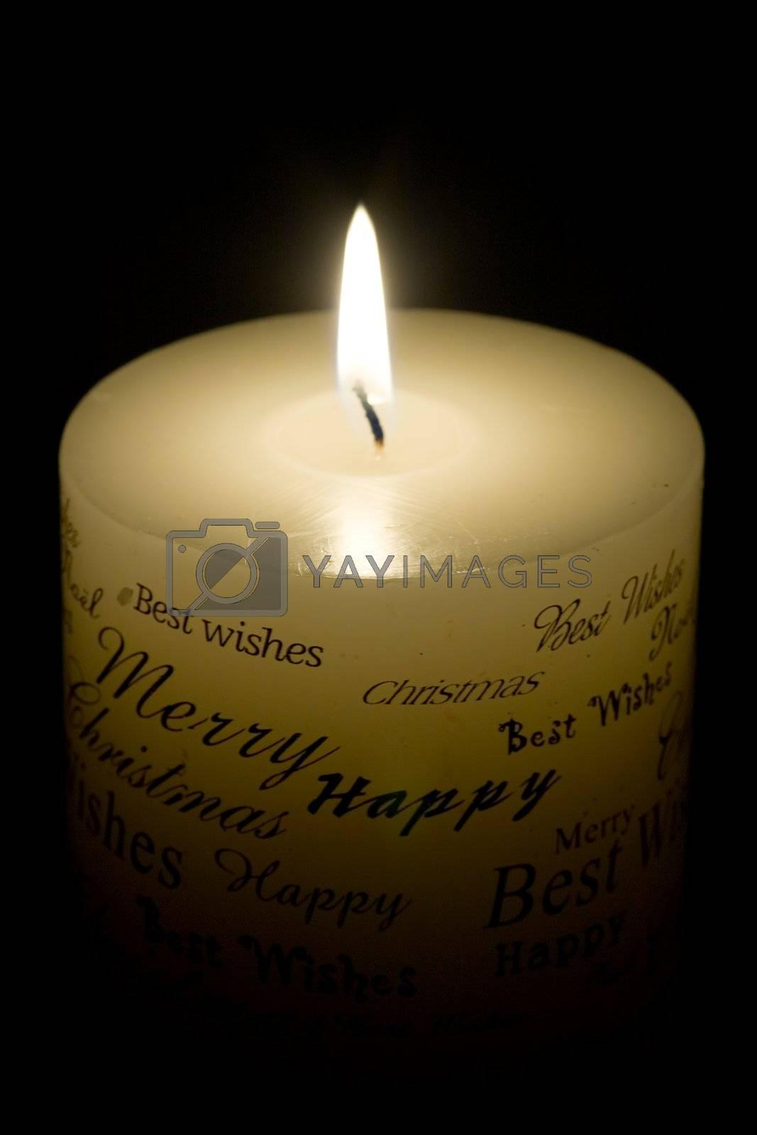 Lit white Christmas candle on black background