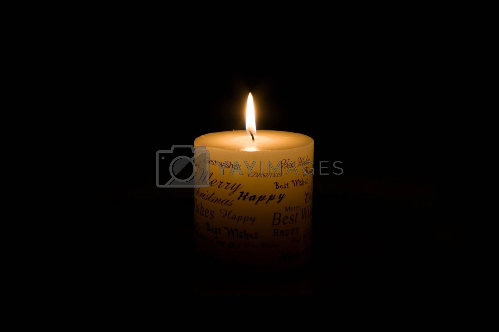 White Christmas candle lit on black background