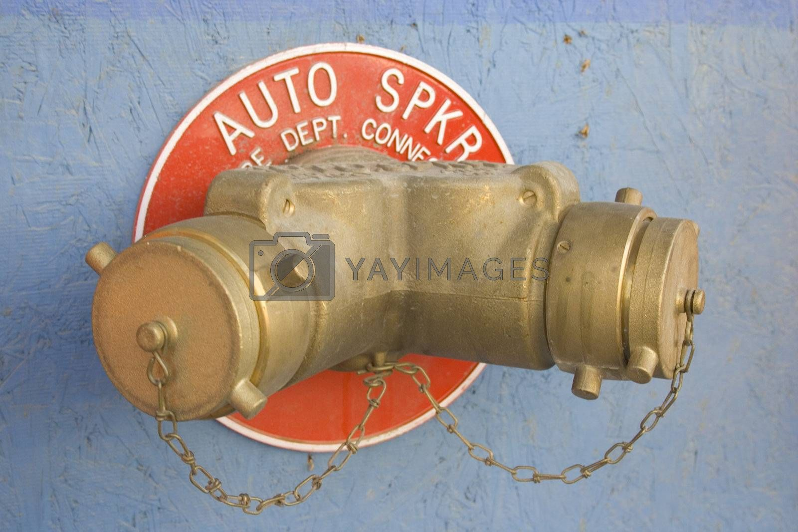 A fire department water valve on a building.
