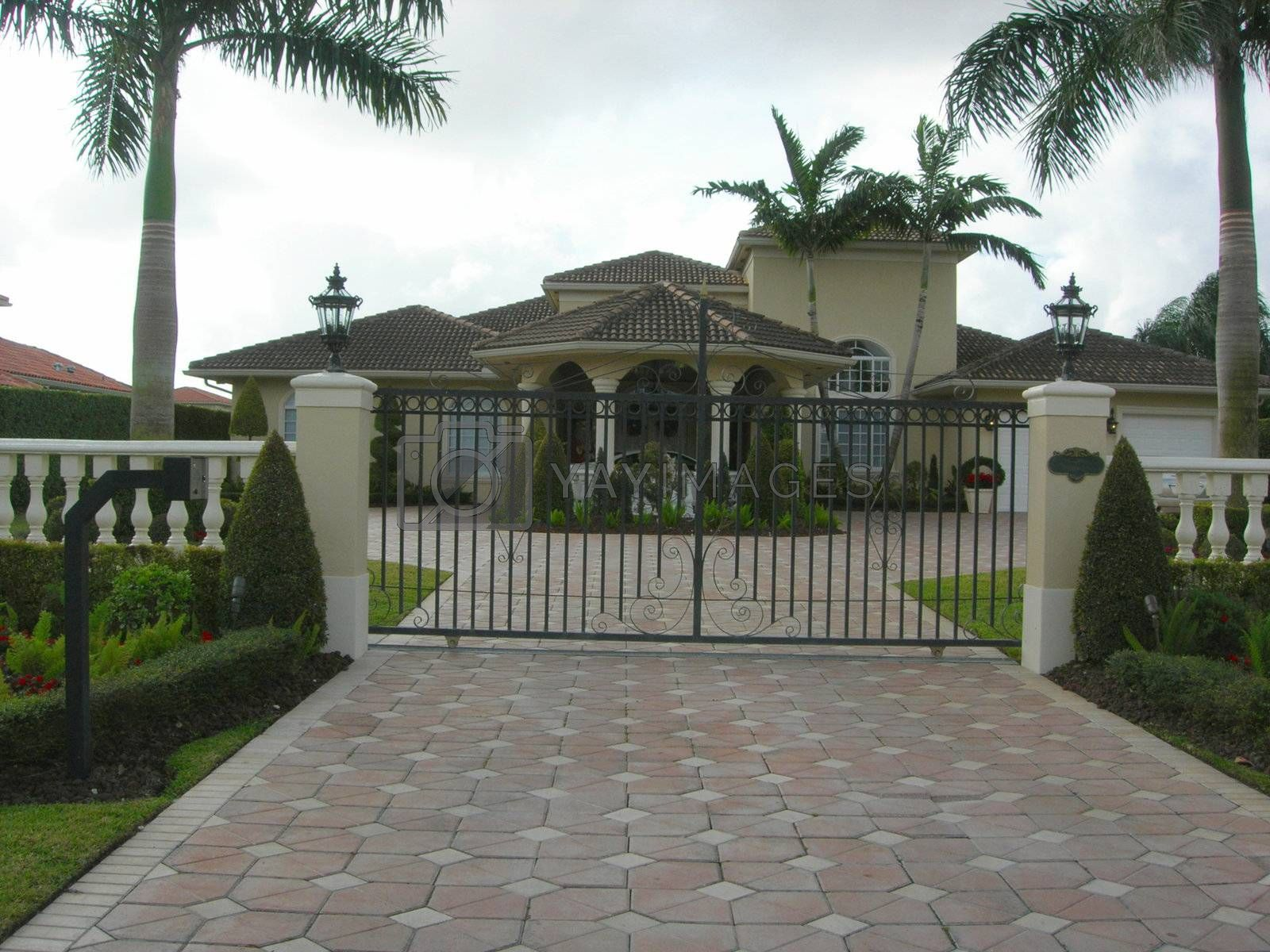 Mediterranean House with pavers, iron gate and landscaping