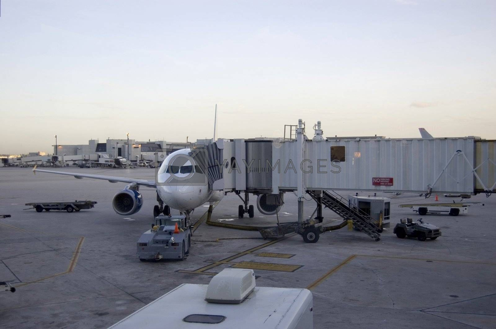Airport Scene Showing airplane and different tractors and jet bridge