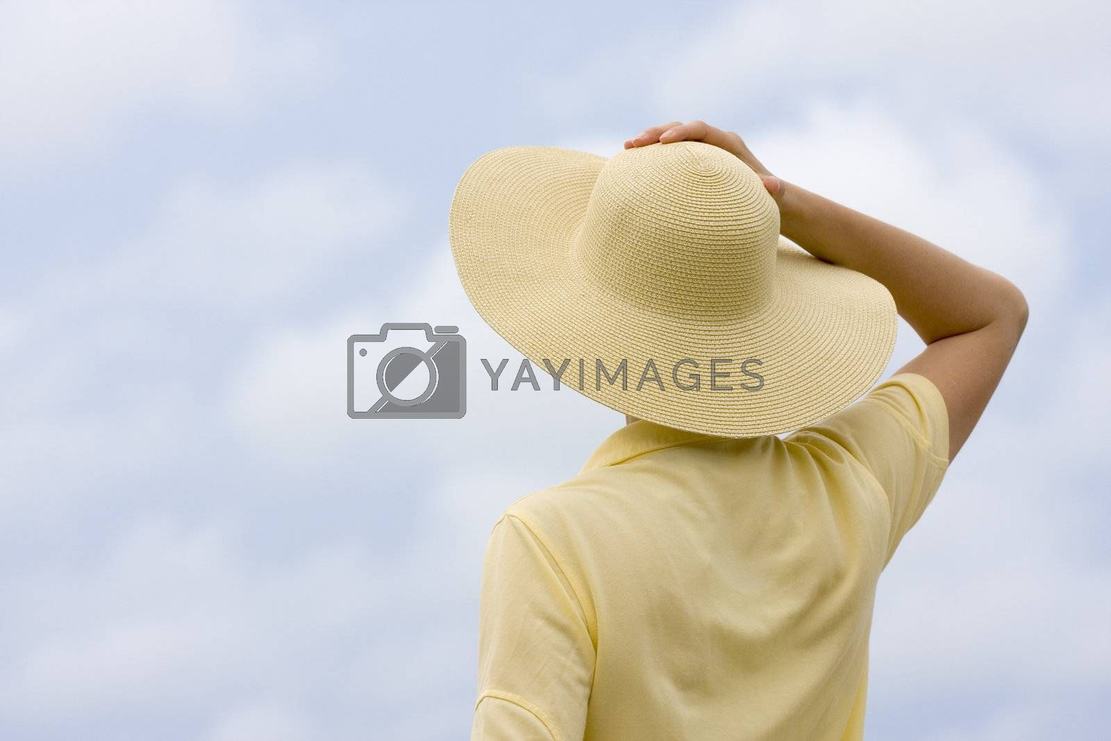 Womann with yellow hat and shirt in front of a sky with clouds
