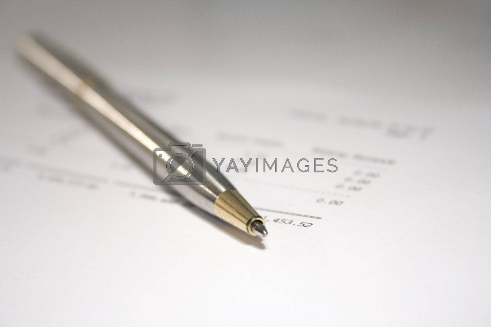 A pen laying on top of financial paperwork.