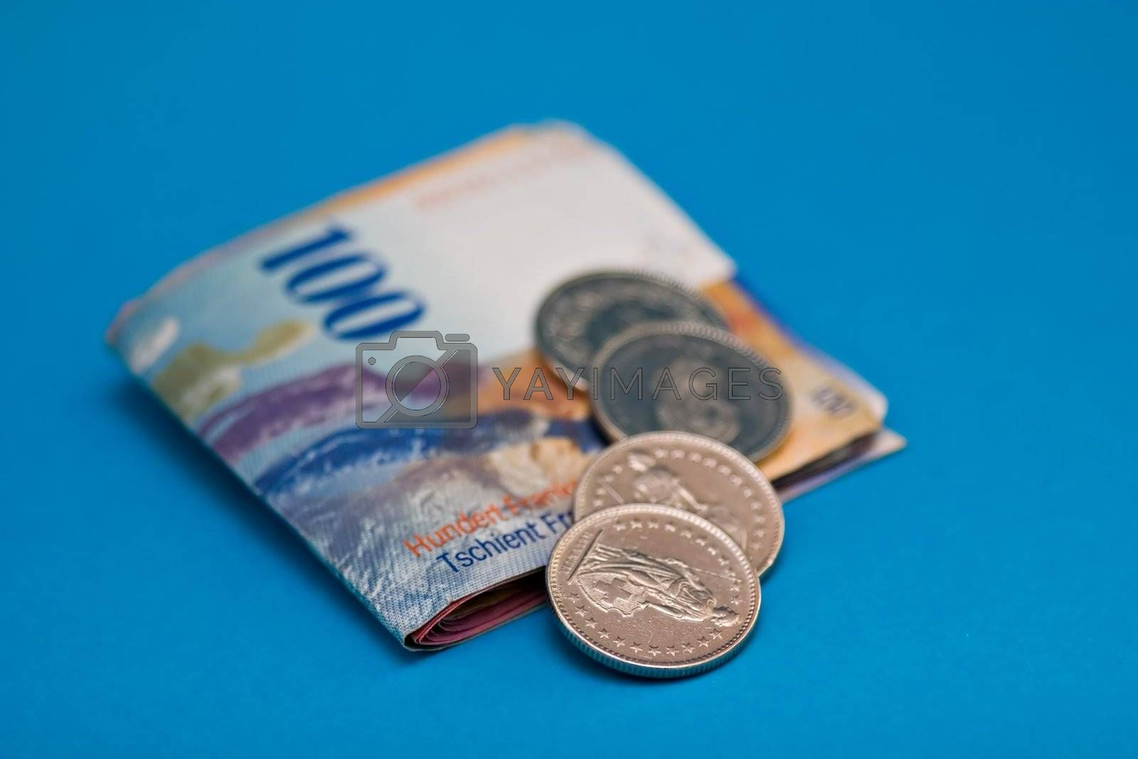 Swiss Franc Bills and Coins on blue background