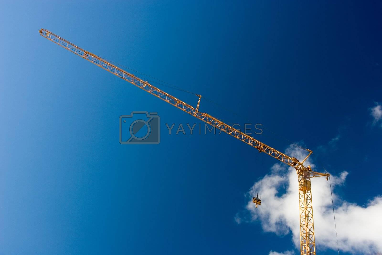 Yellow crane against deep blue sky.