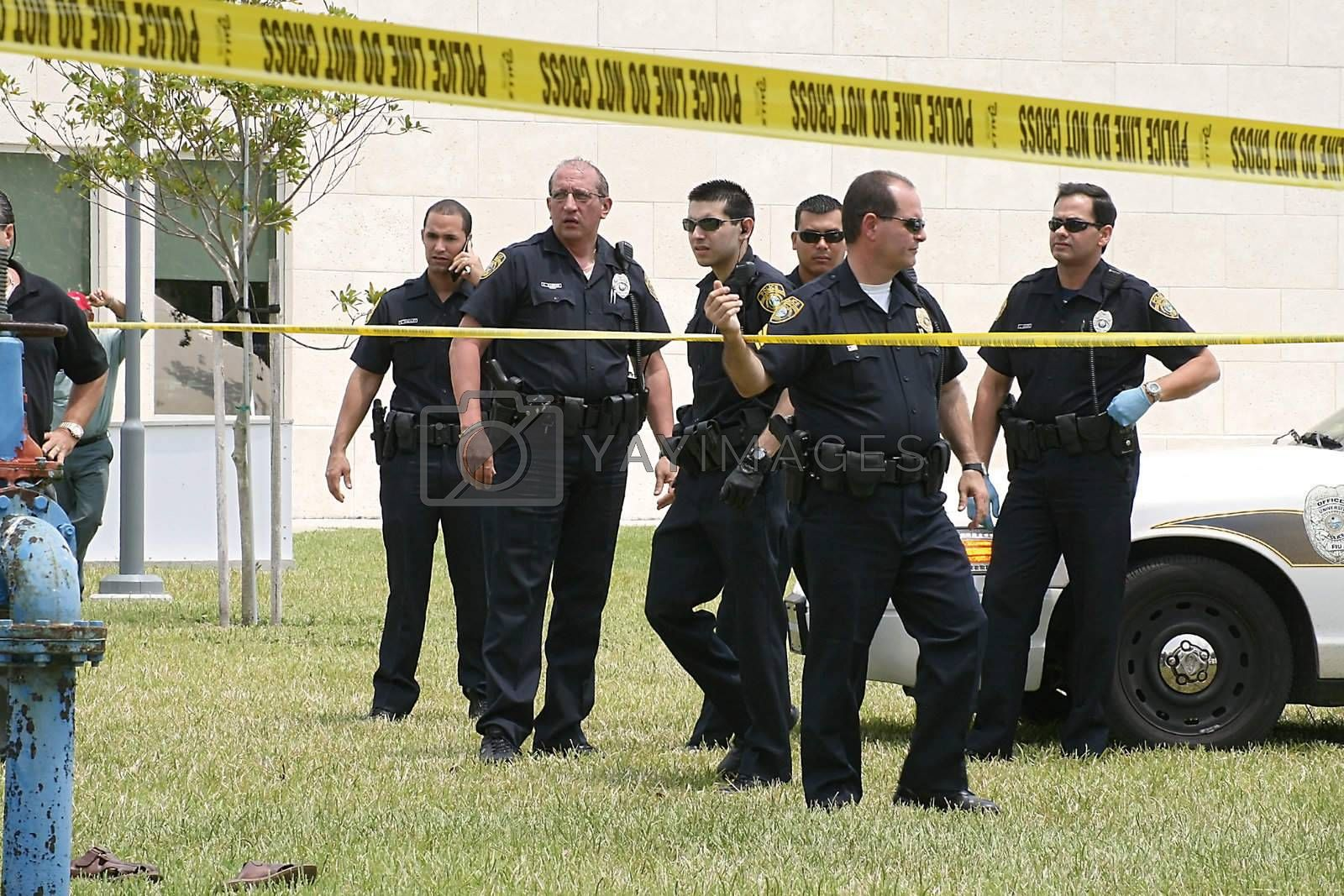 Police on a university campus gather after a car chase ends in a crash.