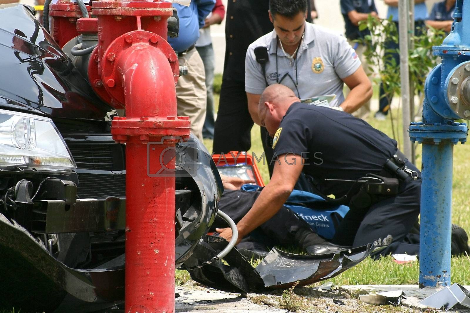 A paramedic aids a police officer injured after a car chase ends in a crash on a university campus.