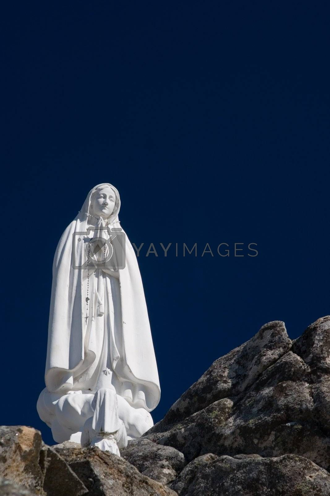 Statue of the Virgin Mary (Our Lady of Fatima) with deep blue sky.