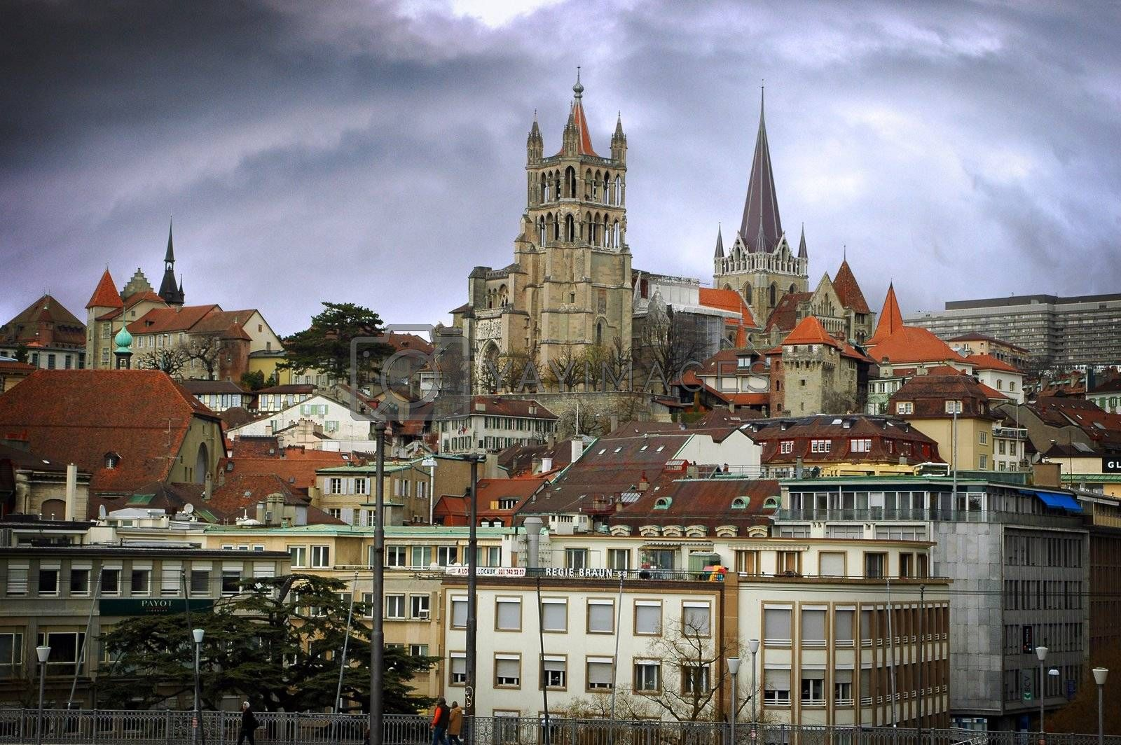 Landscape image of Lausanne showing steeples with a dramatic sky.