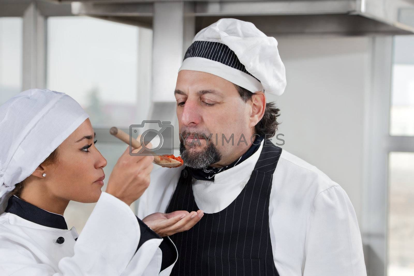 young chef and mature chef tasting tomato sauce.