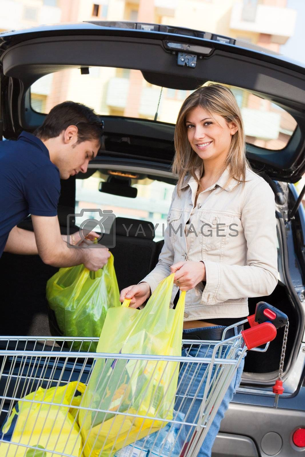 young couple arranging shopping bags in car