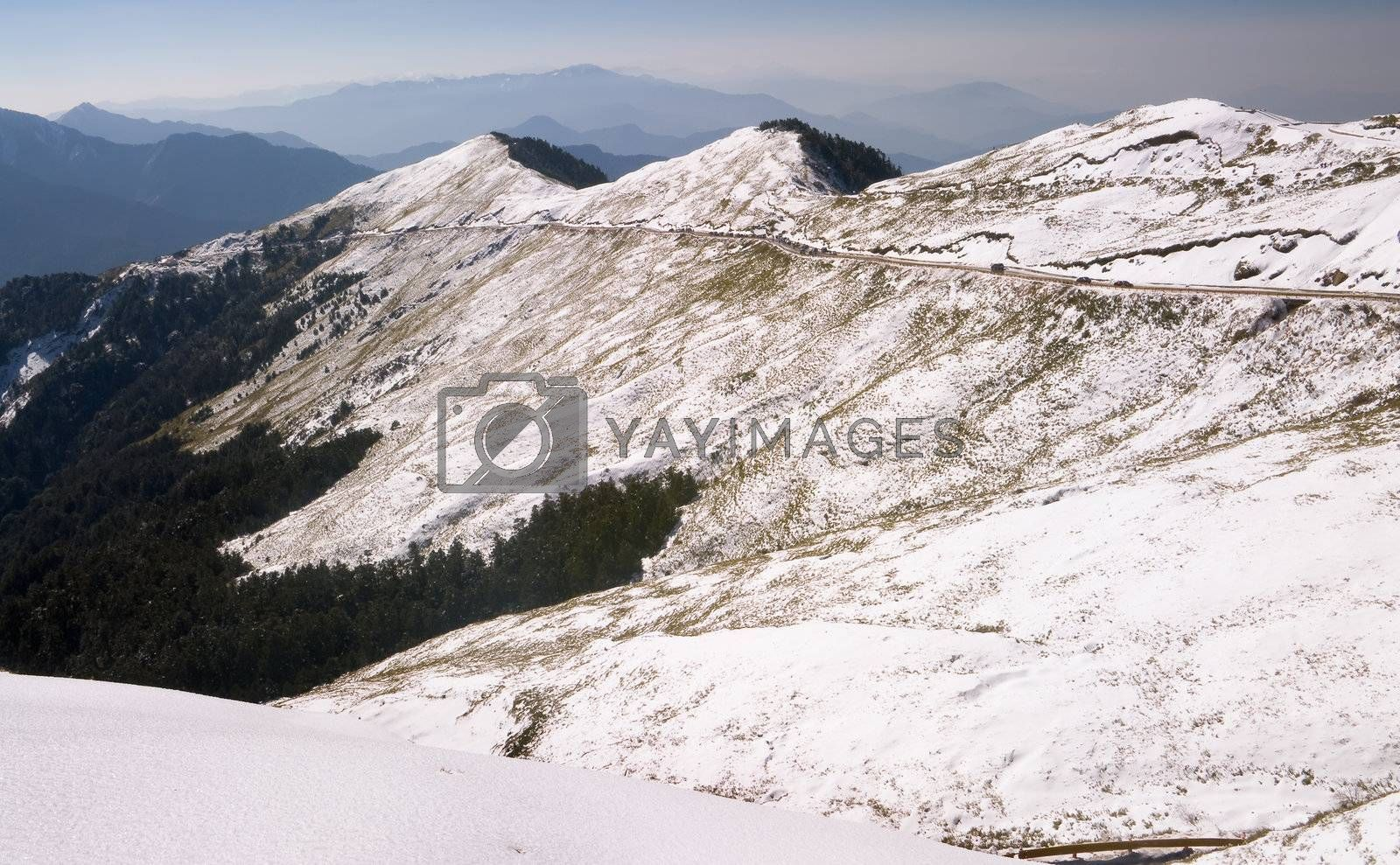 Snow white landscape with mountain transport road and forest.