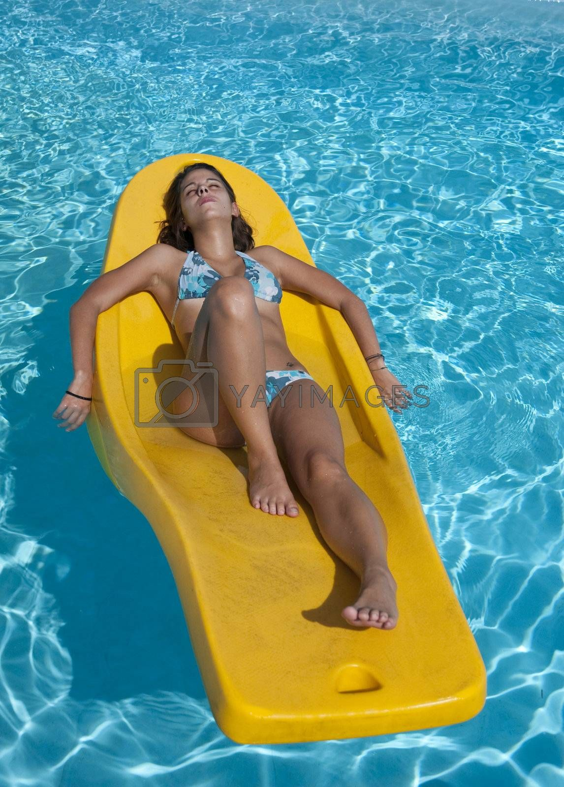 Young woman lying in the sun on a floating mattress
