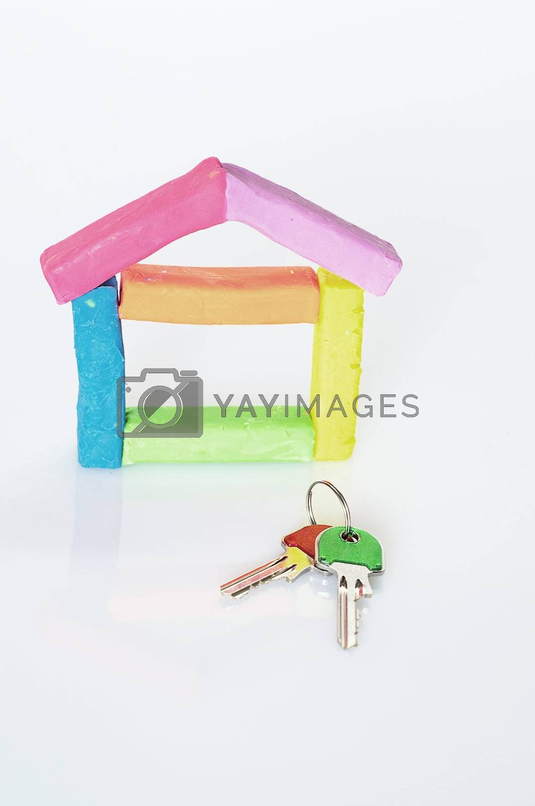 house composed of colored clay on a white background with two keys of different colors