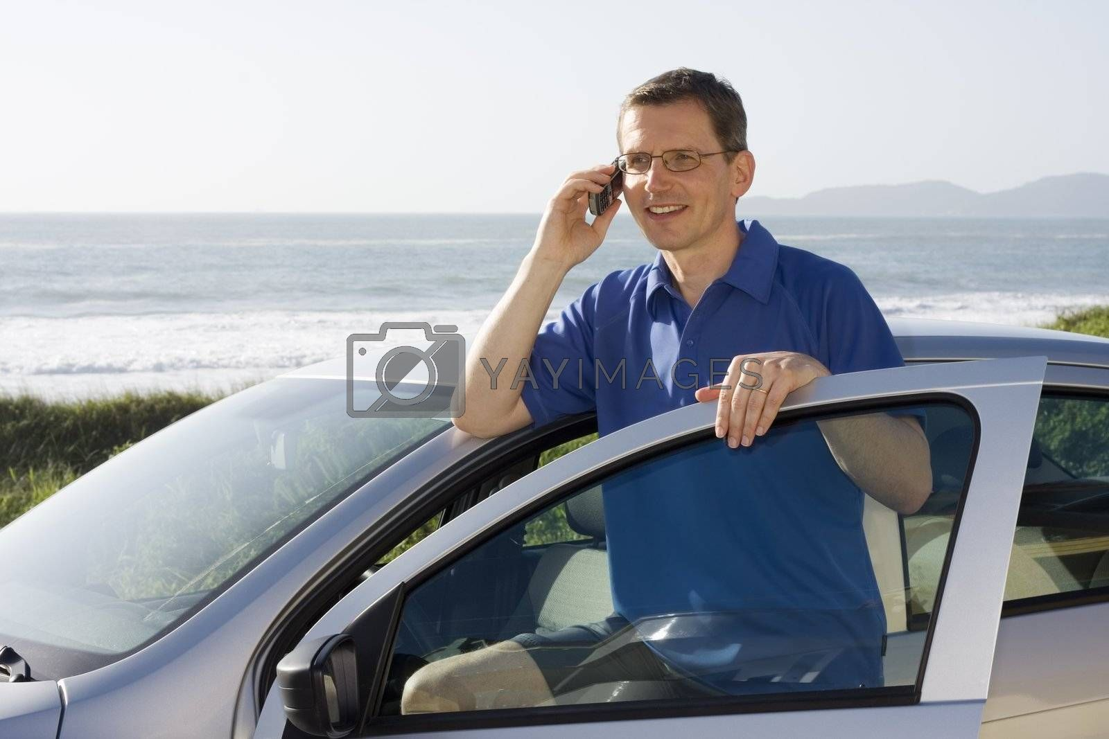 Man talking on cell phone beside a car at the sea