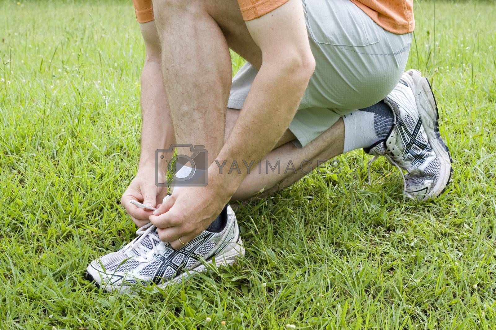 Jogger or runner tying his shoes in green grass