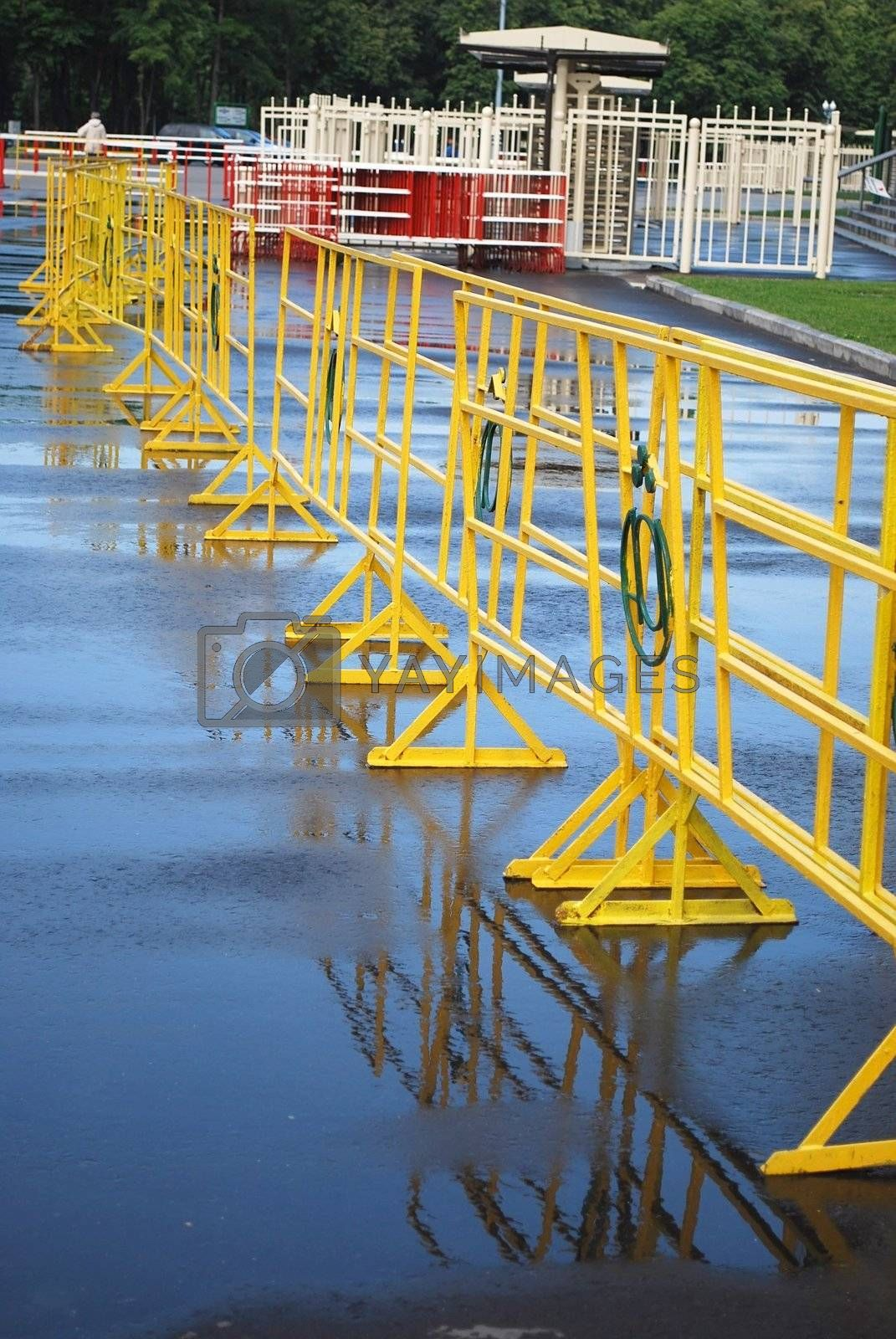 Bright yellow crowd control fence with reflection after rain