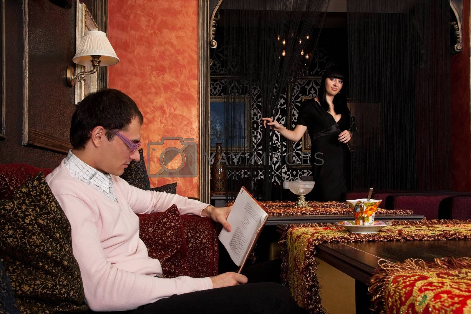 Young couple in luxury interior. He is reading book