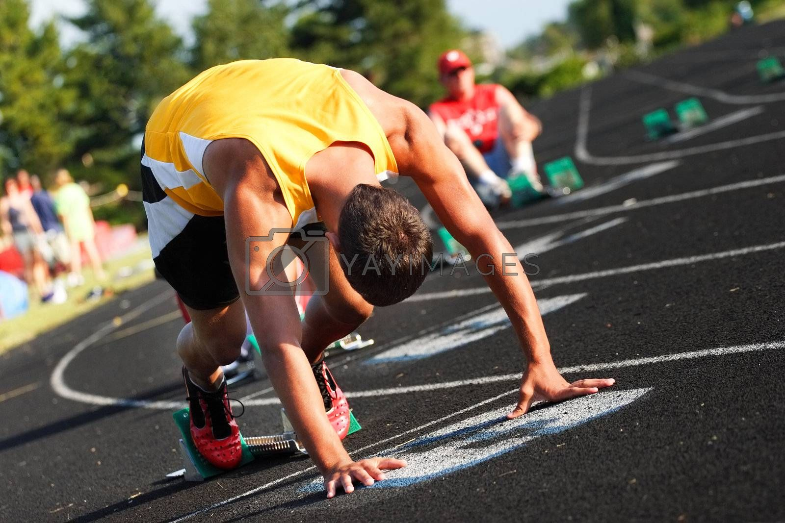 a runner waits on his mark during a relay race